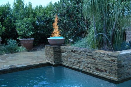 fire pit with colored fire stones by pool teakwoodcentral